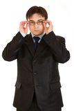 Modern businessman straightening eyeglasses Royalty Free Stock Image