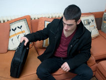 Modern businessman teenager dressed in a black coat and black pants with a bag for laptop. Novi Sad, Serbia Stock Image