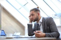 Modern businessman thinking about something while sitting in the office stock image