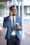 Modern businessman walking and talking on mobile phone Stock Photos