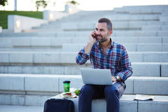 Modern businessman working and talking on the phone outdoors Stock Image