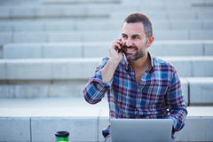 Modern businessman working and talking on the phone outdoors Royalty Free Stock Photography