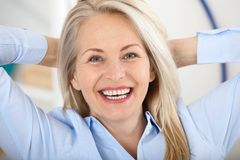 Modern businesswoman. Beautiful middle aged woman looking at camera with smile while siting in the office. Female face close-up stock photography