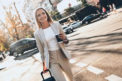 Modern businesswoman. Beautiful young woman in suit pulling luggage and smiling while walking outdoors royalty free stock photography