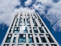 Modern byggnad av exponeringsglas och betong ansar till molnen Royaltyfri Bild
