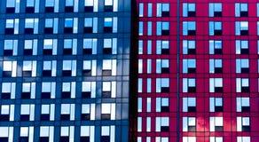 Modern byggnad för två färg som är röd och som är blå med blåa och svarta fönster för ljus - arkivfoton