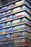 Modern byggnad med kulöra och numrerade glass balkonger Arkivfoton