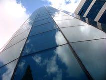 Modern byggnad som göras av exponeringsglas som reflekterar molnen Arkivbilder