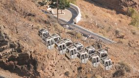 Modern cable cars carrying travellers up and down on Santorini island, tourism. Stock footage stock footage