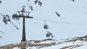 Modern cable cars moving tourists up and down in snowy mountains, ski resort. Stock footage stock footage