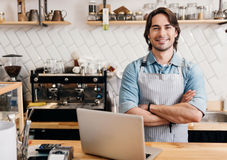 Modern cafe business. Modern barista. Smiling and happy male barista using laptop and smiling at a camera at coffee shop Stock Images