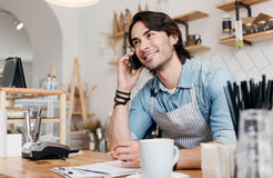 Modern cafe business. Always connected. Cheerful and content male barista talking per mobile phone and writing something down at coffee shop Royalty Free Stock Image