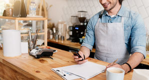 Modern cafe business. Keeping in touch. Cropped image of smiling male barista using mobile phone and writing something down at coffee shop Stock Image