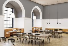 White and gray cafe interior side. Modern cafe interior with white and gray walls, a wooden floor, round gray and long wooden tables, yellow sofas and black and Stock Photos