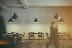 White brick cafe interior toned. Modern cafe interior with wooden tables and chairs near white brick walls. Original ceiling lamps. Business people 3d rendering Royalty Free Stock Photography