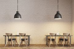 White brick cafe interior close up. Modern cafe interior with wooden tables and chairs near white brick walls. Original ceiling lamps. A close up. 3d rendering Royalty Free Stock Photo