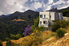 Modern California Dream House in the Mountains. White modern mountaintop mansion home overlooks a beautiful wooded canyon in a southern California mountain range Royalty Free Stock Image