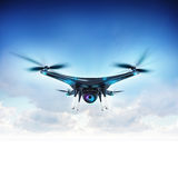 Modern camera drone in flight with blue sky background Stock Photos