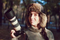 Modern camera with a large lens in hand of young photographer girl and ready to take photo. royalty free stock photo