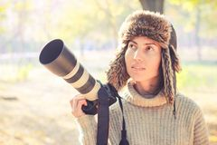 Modern camera with a large lens in hand of young photographer girl and ready to take photo. royalty free stock photos