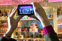 Modern camera, old fashioned christmas. Woman taking pictures of a Fifth Avenue shop window festively decorated for the Christmas season. The store front windows royalty free stock images