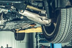 Modern Car in Auto Service. Vehicle on a Lift Awaiting Repair by Professional Mechanic. Automotive Industry royalty free stock photography