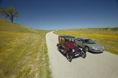 A modern car driving by a maroon Model T on a scenic road surrounded by spring flowers off of Route 58, Shell Road, CA Stock Images