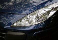 Modern car headlight. The complex headlamps of a modern car lit by dappled sunlight through trees Royalty Free Stock Photo