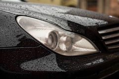 Modern car headlights with water drops. Stock Photos