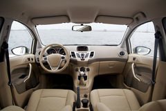 Modern car interior. Wide view of modern car interior with light-colored decoration stock images