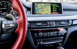 Modern car interior, red steering wheel with media phone control buttons, navigation, screen multimedia system background Stock Image
