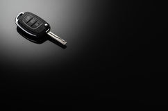 Modern car keys isolated on black reflective background. With copy space for text or design elements. Folding key with remote alarm and trunk opening Stock Image