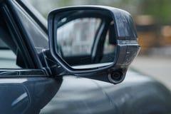 Modern car side mirrors with indicator built in honda lane watch camera. Grey sedan foldable side mirror external with built in indicator slit and camera for Royalty Free Stock Photos