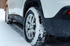Modern car on snowy road, closeup view. Winter season royalty free stock photography
