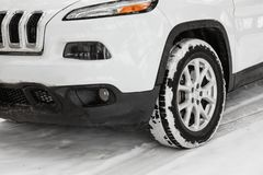 Modern car on snowy road, closeup view. Winter season royalty free stock images
