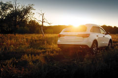 Modern car stand on off-road at sunset Royalty Free Stock Photo