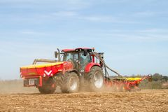 Modern case tractor drilling seed in field Stock Photo