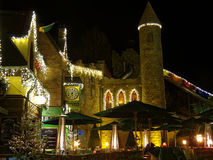 Modern castle building Irish scene by night. The latest themed area Ireland in Europa Park Rust, Germany, with the buildings brightly lighted at Christmas by Royalty Free Stock Image
