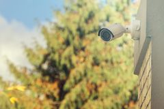 Modern CCTV camera on building wall, foliage background stock photography