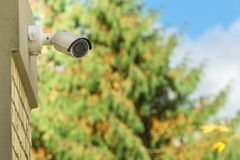 Modern CCTV security camera on building wall, foliage background stock photo