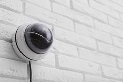 Modern CCTV security camera on white brick wall. Space for text royalty free stock photo