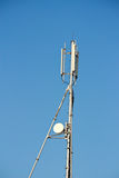 Modern cell and antenna with flat parabola. On blue sky Royalty Free Stock Images
