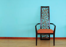 Modern Chair. Modern wood chair against a blue wall Royalty Free Stock Image