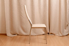 Modern chair standing in front of curtains background Royalty Free Stock Photography