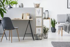 Modern chair with wooden legs by an industrial desk with books b stock photos