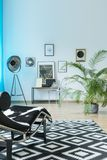 Modern chaise lounge in apartment. Modern chaise lounge on black and white carpet in apartment with lamp and plant royalty free stock photo