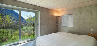 Modern chalet, bedroom. Interior of a modern chalet in cement, bedroom royalty free stock photos