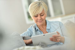 Modern charming senior woman using tablet Stock Images