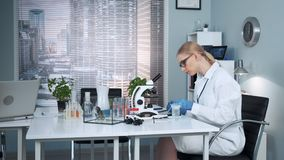 In modern chemistry lab female research scientist using pipette. To drop fertilizers on slider and then examining it under magnifying glass stock video footage