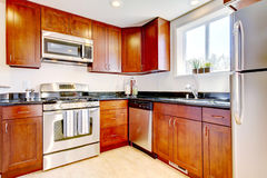 Modern cherry kitchen with steal appliances. Royalty Free Stock Images